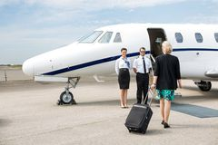 Businesswoman With Luggage Walking Towards Private. Rear view of businesswoman with luggage walking towards private jet while pilot and airhostess standing by Royalty Free Stock Photo