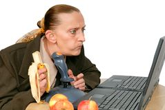 Businesswoman lunchbreak. Businesswoman enjoying her lunch hour and intensively peering at her PC, wanting to do a PC game. Eating a healthy low calories fruit Royalty Free Stock Images