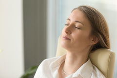 Businesswoman lying on back chair with closed eyes. Tired woman lying on back chair with closed eyes. Businesswoman doing deep relaxation exercises during hard royalty free stock photography