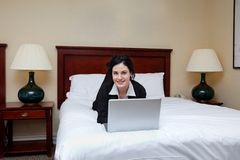 Businesswoman Lying on Bed With Laptop Stock Photos