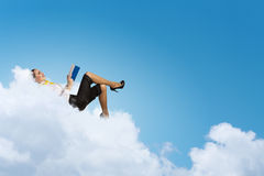Businesswoman lying on clouds Royalty Free Stock Photography