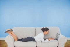 Businesswoman lying on couch using laptop Royalty Free Stock Photo