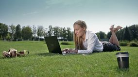 Businesswoman lying on green grass with laptop stock footage
