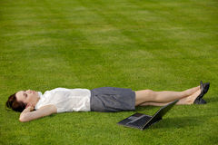 Businesswoman lying in park with laptop Stock Photography