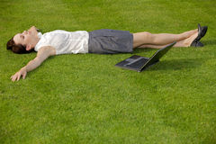 Businesswoman lying in park with laptop Royalty Free Stock Photos