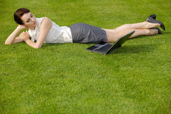 Businesswoman lying in park with laptop Stock Images