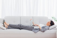 Businesswoman lying on sofa using her laptop Royalty Free Stock Photo