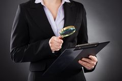 Businesswoman with  magnifying glass and clipboard. Close-up Of Businesswoman Looking Through Magnifying Glass To Clipboard Royalty Free Stock Image