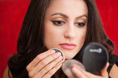 Businesswoman with a make-up mirror. Businesswoman doing her make-up with a make-up mirror Stock Images