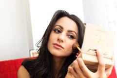 Businesswoman with a make-up mirror. Businesswoman doing her make-up with a make-up mirror Royalty Free Stock Images