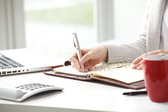 Businesswoman makes a note in notebook. Stock Image