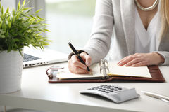 Businesswoman makes a note in notebook. Royalty Free Stock Photography