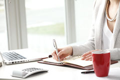 Businesswoman makes a note in notebook. Royalty Free Stock Images