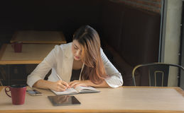 Businesswoman makes a note in notebook. Businesswoman  write strategic planning on notebook./Businesswoman makes a note in notebook Royalty Free Stock Photography