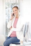 Businesswoman making call at office Royalty Free Stock Photography