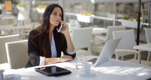 Businesswoman making a call at a restaurant Royalty Free Stock Photo