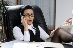 Businesswoman making conversation. Business woman  making conversation on cell phone  and studying news in office Royalty Free Stock Image