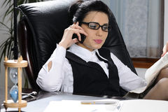 Businesswoman making conversation. Business woman  making conversation on cell phone  and studying news in office Royalty Free Stock Photos