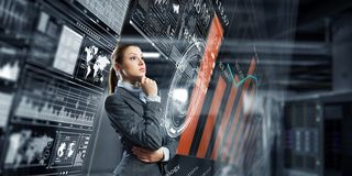 Businesswoman making desicion. Thoughtful businesswoman with hand on chin looking at media panel Stock Image