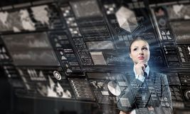 Businesswoman making desicion. Thoughtful businesswoman with hand on chin looking at media panel Royalty Free Stock Photos