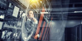 Businesswoman making desicion. Thoughtful businesswoman with hand on chin looking at media panel Stock Images