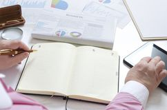 Businesswoman making financial planning at her workplace. Blank notebook, business documents and other stuff ath the office desk stock photos