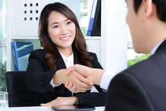 Businesswoman making handshake with a businessman Stock Image