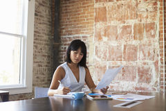 Businesswoman Making Notes On Document In Boardroom Stock Photos