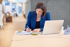 Businesswoman making notes at her desk with laptop open Royalty Free Stock Photography