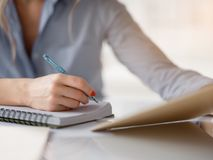 Businesswoman making notes in notebook. Close up of female hand writing down the information from pad. Woman is sitting at desktop Stock Photography