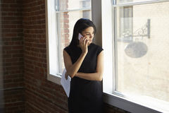 Businesswoman Making Phone Call Standing By Office Window Stock Photography