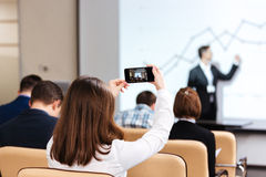 Businesswoman making video with mobile phone on business conference Stock Photo