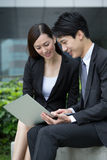 Businesswoman and man look at the laptop computer Stock Images