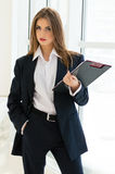 Businesswoman in man's suit & shirt writing with pen at her office fashion styled Royalty Free Stock Images