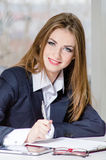 Businesswoman in man's suit signing with pen at her office fashion styled Royalty Free Stock Images