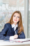 Businesswoman in man's suit signing with pen at her office fashion styled Royalty Free Stock Image