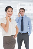 Businesswoman and man using cellphones in office Stock Images
