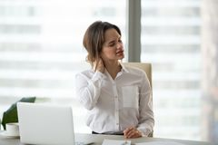 Businesswoman massaging neck muscles to relieve pain after seden. Tired businesswoman feels fatigue massaging tensed muscles of stiff neck trying to relieve pain stock photography