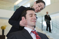 Businesswoman massaging stressed executive's head Stock Images