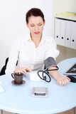 Businesswoman measuring her blood pressure. Royalty Free Stock Image