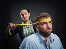 Businesswoman measuring man's head Stock Photo