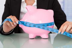 Businesswoman measuring piggybank at desk Royalty Free Stock Photo