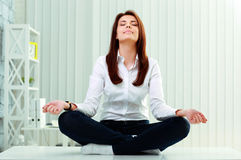 Businesswoman meditates on the table stock image