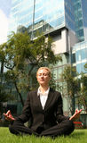 Businesswoman meditating. In the grass in front of office buildings Stock Photos
