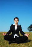 Businesswoman meditating. A beautiful young businesswoman mediating outdoors in a field with a blue sky Stock Image