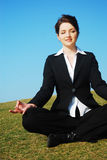 Businesswoman meditating. A beautiful young businesswoman meditating in a field Royalty Free Stock Photography