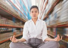 Businesswoman Meditating against motion blur background. Digital composite of Businesswoman Meditating against motion blur background Royalty Free Stock Photo