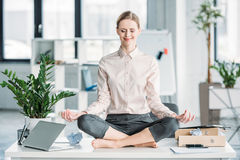Businesswoman meditating in lotus position on messy table in office. Happy businesswoman meditating in lotus position on messy table in office Royalty Free Stock Image
