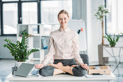 Businesswoman meditating in lotus position on messy table in office. Happy businesswoman meditating in lotus position on messy table in office Royalty Free Stock Images