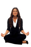 Businesswoman meditating in lotus posture Stock Images